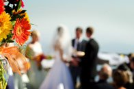 Bride and groom in background saying their vows. Flowers in foreground sharp focus. Bride and groom blurred